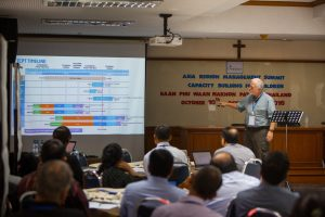 Ed Anderson, Compassion International's chief financial officer, discusses information systems with ministry workers in Thailand in October. The ministry's field offices in 26 countries work with nearly two million children.